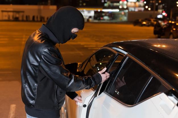 Ladrón masculino con pasamontañas en la cabeza abriendo la puerta del coche