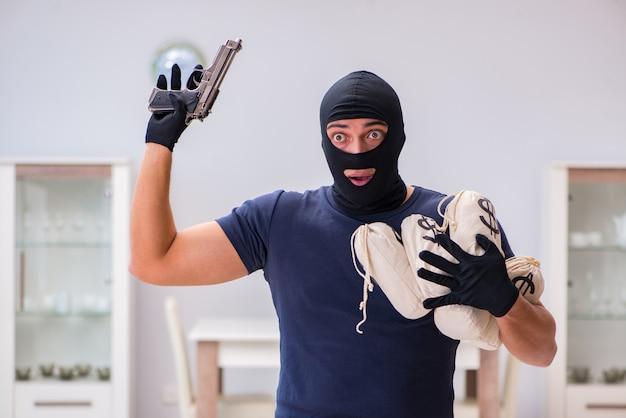 Ladrón con pasamontañas robando cosas valiosas