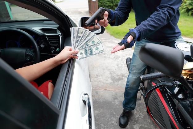 Ladrón con pistola en motocicleta robando dinero de mujer en el auto