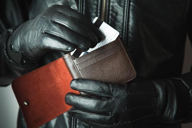 Ladrón sacando la tarjeta de la billetera