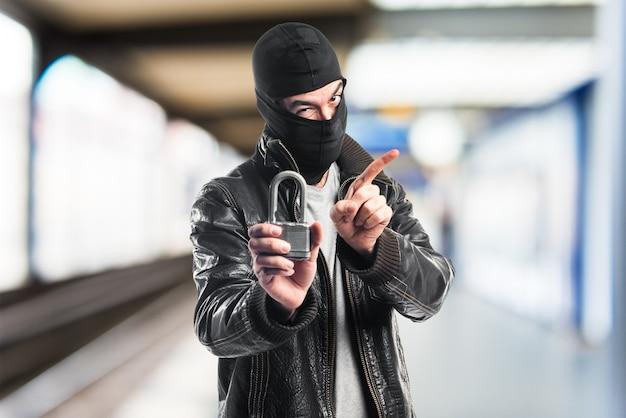 Ladrón sosteniendo el candado de la vendimia