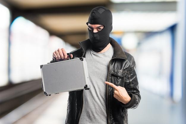 Ladrón sosteniendo un maletín