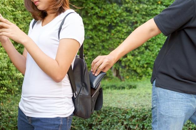 Ladrón tratando de robar la billetera en la mochila y alejarse.