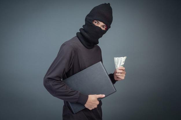 Los ladrones tienen tarjetas de crédito usando una computadora portátil para actividades de piratería de contraseñas.