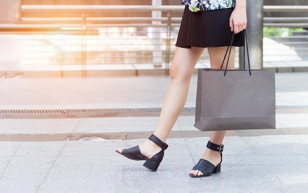 Lady está caminando en la calle y sosteniendo la bolsa de compras en su mano.