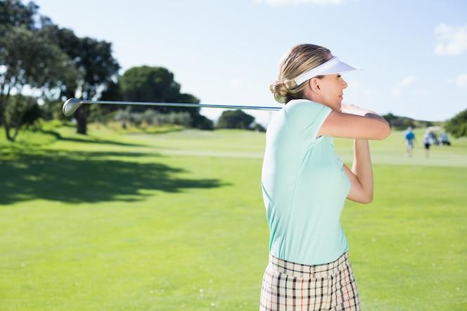 Lady golfista jugando al fútbol por el día