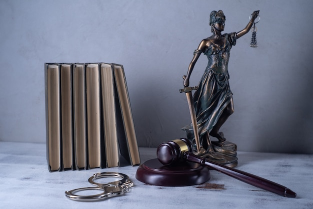 Lady justice, martillo del juez, libros, esposas en una mesa de madera antigua