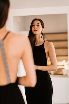 Lady lleva un hermoso vestido negro mirándose al espejo