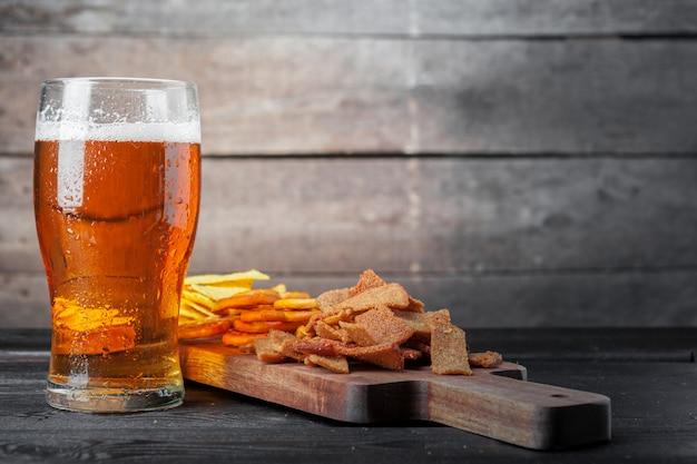 Lager cerveza y aperitivos en mesa de madera. nueces, papas fritas, pretzel