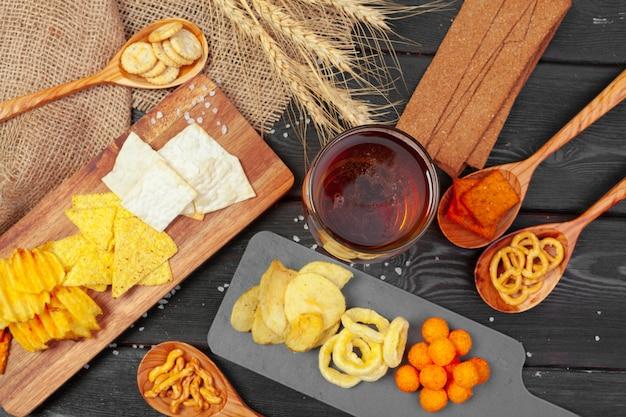 Lager cerveza y aperitivos en mesa de madera.