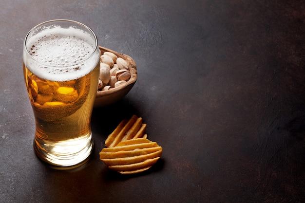 Lager de cerveza y aperitivos en mesa de piedra.