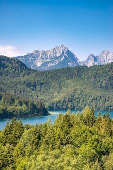 Lago azul alpsee en el bosque verde y montañas de los alpes. fussen, baviera, alemán