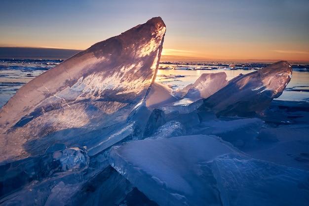 Lago baikal al atardecer, todo está cubierto de hielo y nieve, espeso hielo azul claro