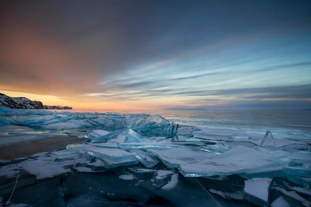 Lago baikal al atardecer, todo está cubierto de hielo y nieve.
