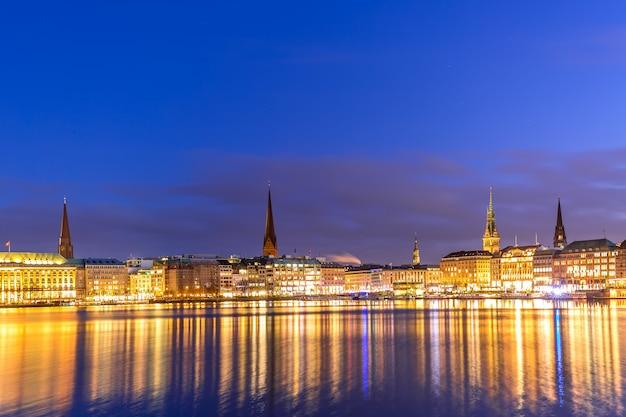 Lago binnenalster con el centro de la ciudad iluminada en hamburgo, alemania, durante la puesta de sol crepuscular.
