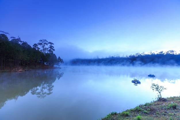 Lago y bosque de pinos en el tiempo de la mañana en