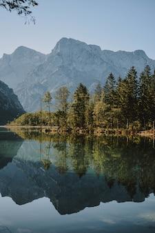 Lago claro con árboles que se reflejan en el agua en la orilla y montañas que rodean la vista