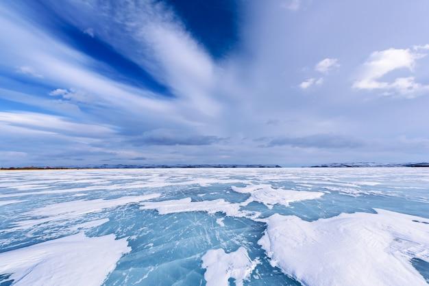 El lago congelado baikal. hermoso estrato de nubes sobre la superficie del hielo en un día helado.