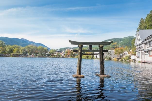 Lago kinrin y puerta japonesa (torii) con el fondo de yufu y el cielo azul en yufuin, oita, kyushu, japón