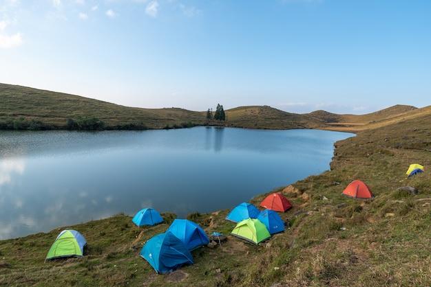 El lago natural en la pradera tiene muchas tiendas de campaña junto al lago.
