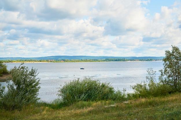 Lago con orilla cubierta de hierba y nubes en el cielo azul.