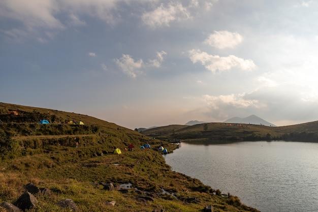 En el lago de la pradera, la gente instaló tiendas de campaña junto al lago;