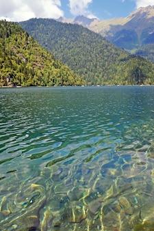 Lago ritsa en montañas en abjasia en un día soleado de verano. el lago de montaña de origen glacial y tectónico en el cáucaso occidental, en la región gudautsky de abjasia.