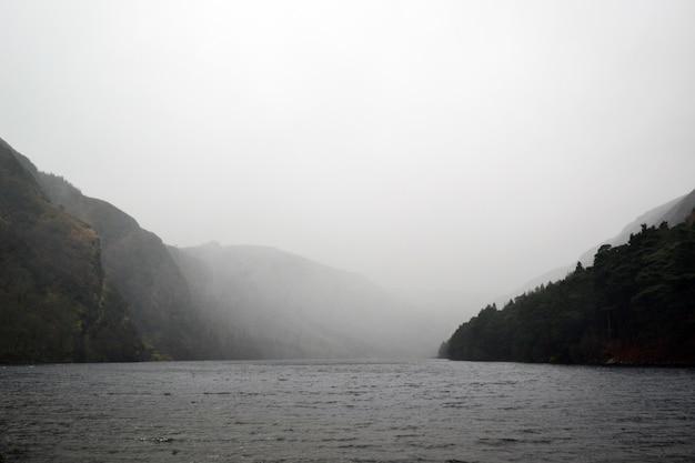 Lago rodeado de colinas bajo el brumoso cielo gris
