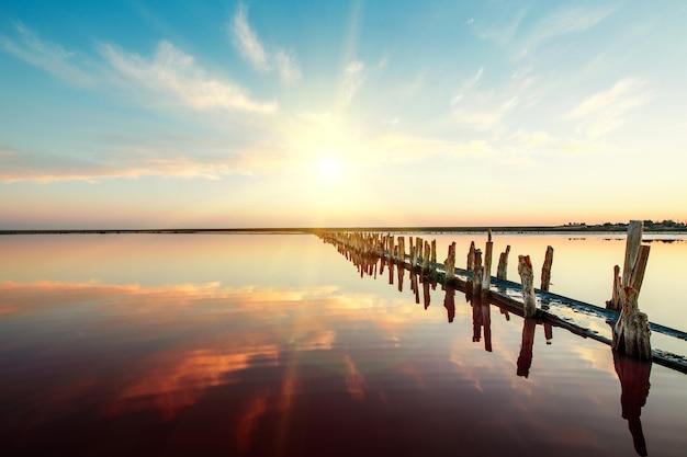 Lago rosa y playa de arena con una bahía de mar bajo un cielo azul con nubes