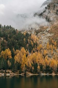 Lago tranquilo y nubes bajas que cubren una montaña áspera cubierta con follaje otoñal colorido