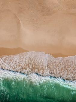 Laguna con olas de mar y playa de arena.