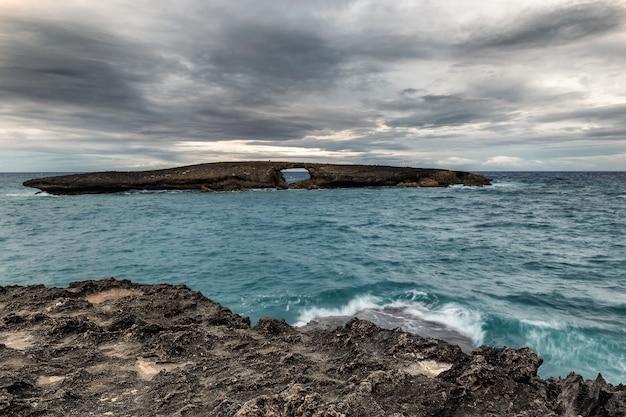 Laie point vista al mar de la roca con un agujero antes del atardecer con cielo gris oscuro