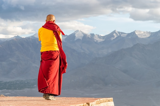 Lama monje tibetano indio parado frente a las montañas