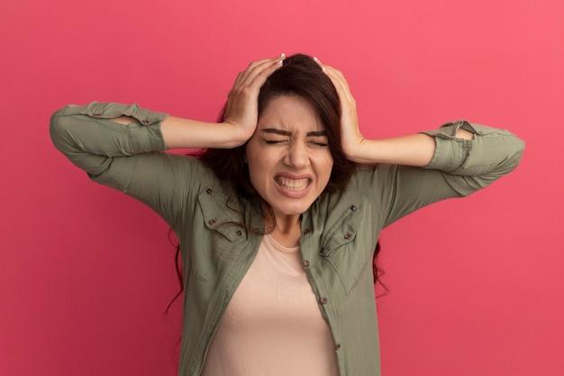 Lamentado con los ojos cerrados joven hermosa vestida con camiseta verde oliva agarró la cabeza aislada en la pared rosa