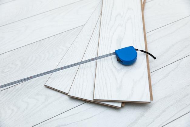 Laminado de madera blanca con cinta métrica en el suelo
