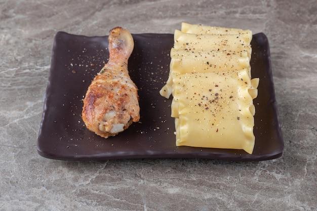 Láminas de lasaña picante junto con muslo de pollo en el plato de madera, en el mármol.