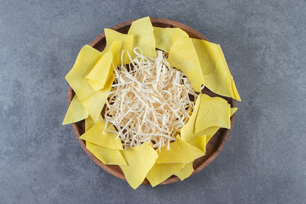 Láminas de queso cecil y lasaña sobre un plato de madera, sobre la superficie de mármol.