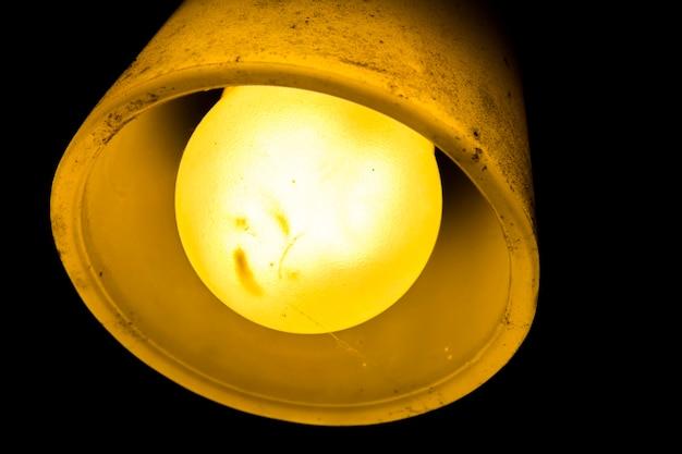 Lámpara con bombilla antigua de luz amarilla brillante tapa sucia