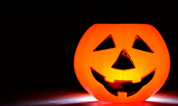Lámpara de cabeza de calabaza de halloween sobre un fondo negro