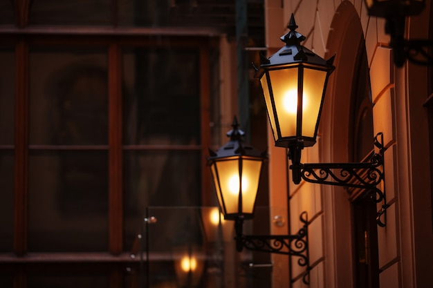 Lámpara de calle antigua en la noche. farolas iluminadas al atardecer. lámparas decorativas. lámpara mágica con una cálida luz amarilla en el crepúsculo de la ciudad. copia espacio