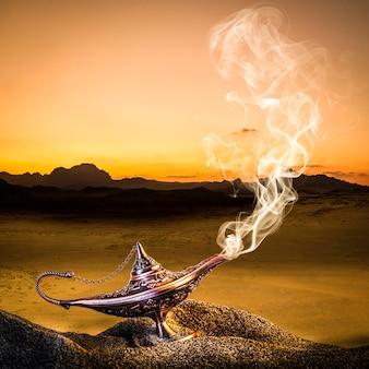Lámpara clásica de aladino de color dorado colocada en la arena de una duna con humo saliendo.
