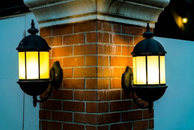 Lámpara contra una pared de ladrillo rojo en la noche.