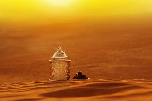 Lámpara y dátiles en la arena con vistas a una hermosa puesta de sol