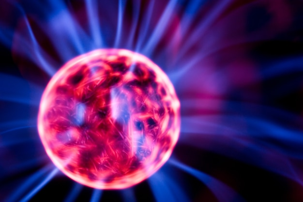 Lámpara de decoración en forma de bola de plasma con electrodos rojos y azules sobre fondo negro, primer plano. tipos inusuales modernos de concepto de iluminación