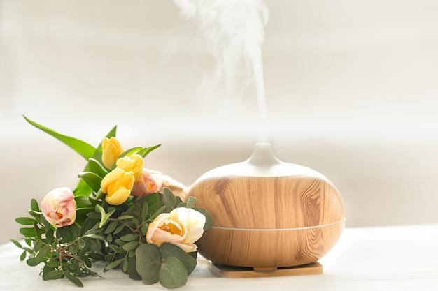 Lámpara difusora de aceite de aroma sobre la mesa en borrosa con un hermoso ramo primaveral de tulipanes.