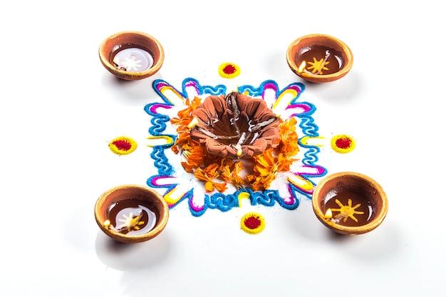 Lámpara diya de arcilla encendida durante el festival de diwali. clay diya en rangoli. festival hindú hindú de las luces llamado diwali.