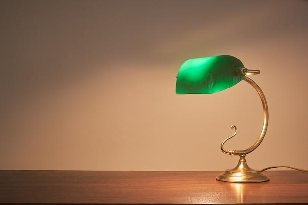 Lámpara de escritorio retro con luz sobre mesa de madera
