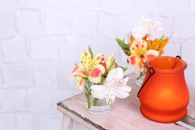 Lámpara de icono brillante con flores en escalera de madera sobre fondo claro
