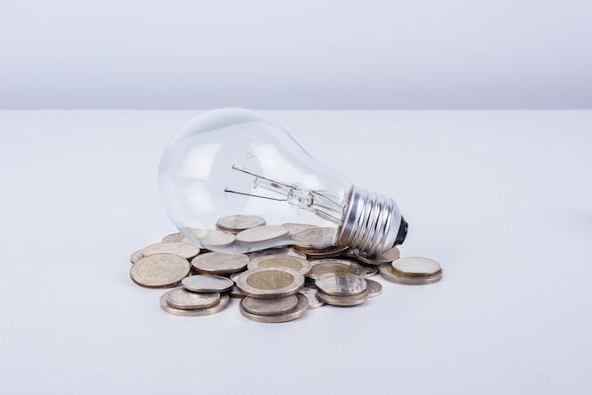 Lámpara incandescente de energía y dinero en el fondo blanco