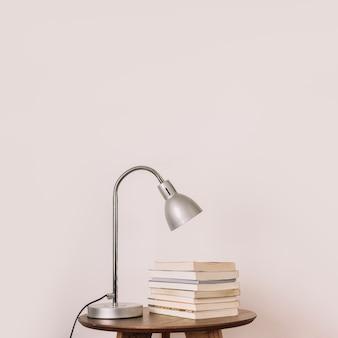 Lámpara y libros cerca de la pared blanca